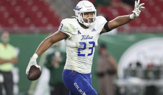 FILE - Tulsa linebacker Zaven Collins (23) celebrates after scoring a touchdown during an NCAA football game in Tampa, Fla., in this Oct. 23, 2020, file photo. Zaven Collins is a small-town player with big-time talent. He was overlooked after a stellar high school career in Hominy, Okla., a town with about 3,500 people. He's got the nation's attention now -- the 6-foot-4, 260-pound linebacker is a finalist for the Butkus and Nagurski Awards.  (AP Photo/Mark LoMoglio, File)