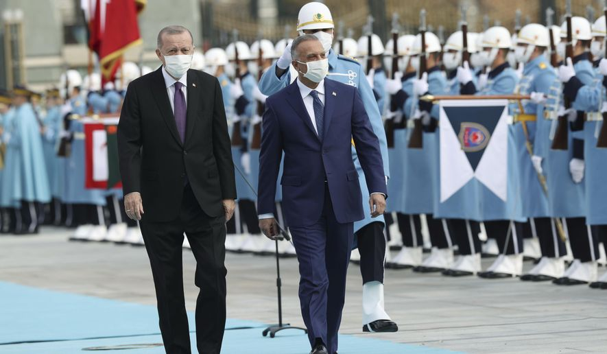 Turkey's President Recep Tayyip Erdogan, left, walks with Iraqi Prime Minister Mustafa al-Kadhimi, centre, as they review an honour guard during a welcome ceremony prior to their meeting at the Presidential Palace in Ankara, Turkey, Thursday, Dec. 17, 2020. Al-Kadhimi is in Turkey on an official visit. (Presidential Press Service via AP, Pool)