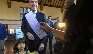 FILE - In this March 7, 2017, file photo, Los Angeles Mayor Eric Garcetti casts his election ballot with his daughter, Maya, in Los Angeles. Garcetti said Thursday, Dec. 17, 2020 that his now 9-year-old daughter, Maya, has tested positive for COVID-19, and that he and his wife are quarantining at home. Garcetti said his daughter Maya felt ill on Monday, developed a fever and tested positive for COVID-19. He said he and his wife, Amy, have tested negative. Garcetti also said that he told the incoming Biden Administration earlier this week that he would not leave Los Angeles. (AP Photo/Nick Ut, File)