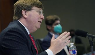 Gov. Tate Reeves responds to questions regarding the holiday social receptions his office planned at the Governor's Mansion, during his COVID-19 news briefing, Wednesday, Dec. 9, 2020 in Jackson, Miss. (AP Photo/Rogelio V. Solis)