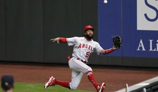 FILE - In this Aug. 5, 2020, file photo, Los Angeles Angels right fielder Jo Adell tries to catch a deep fly ball from Seattle Mariners' Evan White during the seventh inning of a baseball game in Seattle. Angels manager Joe Maddon will not be surprised if Adell starts the upcoming season in the minors after a rough 38-game introduction to the big leagues in 2020. (AP Photo/Elaine Thompson, File)