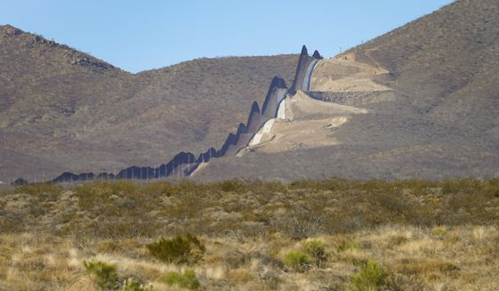 Newly erected border wall separating Mexico, left, and the United States, cuts through through the Sonoran Desert just west of the San Bernardino National Wildlife Refuge, Wednesday, Dec. 9, 2020, in Douglas, Ariz.  Construction of the border wall, mostly in government owned wildlife refuges and Indigenous territory, has led to environmental damage and the scarring of unique desert and mountain landscapes that conservationists fear could be irreversible. (AP Photo/Matt York)