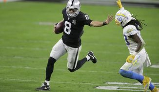 Las Vegas Raiders quarterback Marcus Mariota (8) runs for a gain against Los Angeles Chargers strong safety Rayshawn Jenkins (23) in overtime of an NFL football game, Thursday, Dec. 17, 2020, in Las Vegas. (AP Photo/Isaac Brekken)