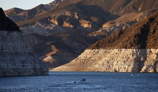 FILE - In this July 20, 2014 file photo, a bathtub ring of light minerals shows the high water line near Hoover Dam on Lake Mead at the Lake Mead National Recreation Area in Nevada. A set of guidelines for managing the Colorado River helped several states through a dry spell, but it's not enough to keep key reservoirs in the American West from plummeting amid persistent drought and climate change, according to a U.S. report released Friday, Dec. 18, 2020. (AP Photo/John Locher, File)