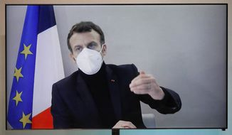 French President Emmanuel Macron is seen on a screen as he attends by video conference a round table for the National Humanitarian Conference (NHC), taken at the Foreign Ministry in Paris,Thursday, Dec. 17, 2020. French President Emmanuel Macron tested positive for COVID-19 Thursday following a week in which he met with numerous European leaders. (Charles Platiau/Pool via AP)