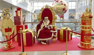 A man wearing a Santa Claus costume checks his mobile phone as he waits to pose for pictures at a mall in Rome, Friday, Dec. 18, 2020. The health ministry reported another 18,236 confirmed cases Thursday, in line with recent days. The government is weighing whether to impose a tighter lockdown over Christmas to prevent gatherings and the ensuing surge in new cases. (AP Photo/Gregorio Borgia)