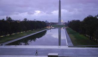 A man walks past the Lincoln Memorial Reflecting Pool and Washington Monument as sunrise approaches on Thanksgiving, Thursday, Nov. 26, 2020, in Washington. (AP Photo/Patrick Semansky)