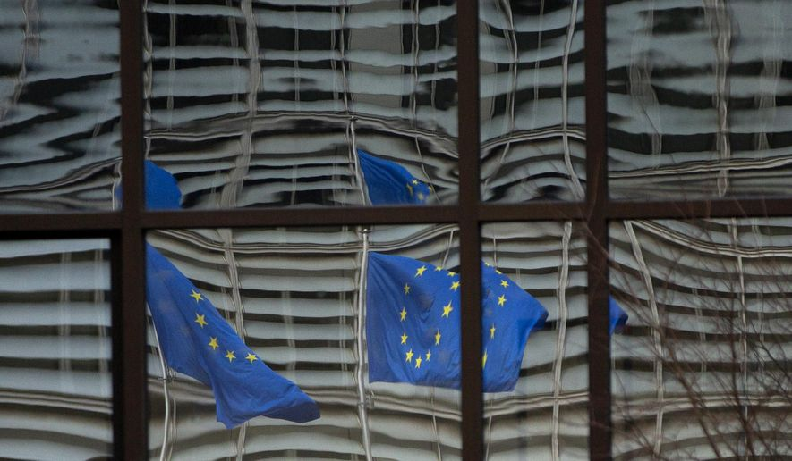 """European Union flags are reflected in a window of the European Council in Brussels, Saturday, Dec. 19, 2020. The European Union and the United Kingdom were starting a """"last attempt"""" to clinch a post-Brexit trade deal, with EU fishing rights in British waters the most notable remaining obstacle to avoid a chaotic and costly changeover on New Year. (AP Photo/Virginia Mayo)"""