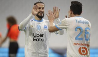 Marseille's Florian Thauvin, right, celebrates his goal with his teammate Dario Benedetto against Rennes during the French League One soccer match between Marseille and Reims at the Stade Velodrome in Marseille, southern France, Saturday Dec. 19, 2020. (AP Photo/Daniel Cole)