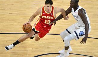 Atlanta Hawks guard Bogdan Bogdanovic (13) drives against Memphis Grizzlies center Gorgui Dieng (14) in the second half of an NBA preseason basketball game Saturday, Dec. 19, 2020, in Memphis, Tenn. (AP Photo/Brandon Dill)