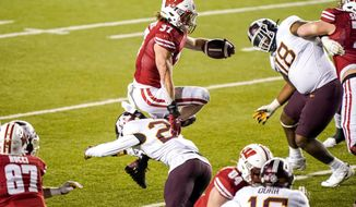 Wisconsin running back Garrett Groshek (37) runs over Minnesota defensive back Tyler Nubin (27) during overtime of an NCAA college football game Saturday, Dec. 19, 2020, in Madison, Wis. (AP Photo/Andy Manis)