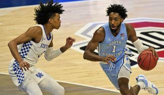 North Carolina's Leaky Black (1) drives past Kentucky's Brandon Boston Jr. (3) in the first half of an NCAA college basketball game, Saturday, Dec. 19, 2020, in Cleveland. North Carolina won 75-63. (AP Photo/Tony Dejak)