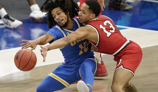UCLA's Tyger Campbell (10) and Ohio State's CJ Walker (13) battle for the ball in the second half of an NCAA college basketball game, Saturday, Dec. 19, 2020, in Cleveland. (AP Photo/Tony Dejak)