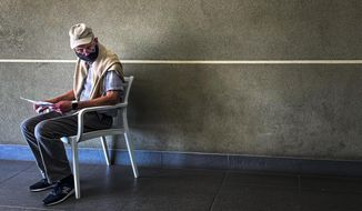 A lone man who was just tested for COVID-19 waits in line to make payment for the test at a private laboratory in Johannesburg, South Africa, Saturday Dec. 19, 2020. South Africa is bracing for its second wave, as many people will travel across provinces for vacations and visiting their families. (AP Photo/Jerome Delay)