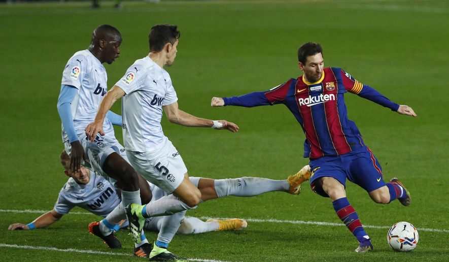 Barcelona's Lionel Messi, right, takes a shot at goal during the Spanish La Liga soccer match between Barcelona and Valencia at the Camp Nou stadium in Barcelona, Spain, Saturday, Dec. 19, 2020. (AP Photo/Joan Monfort)
