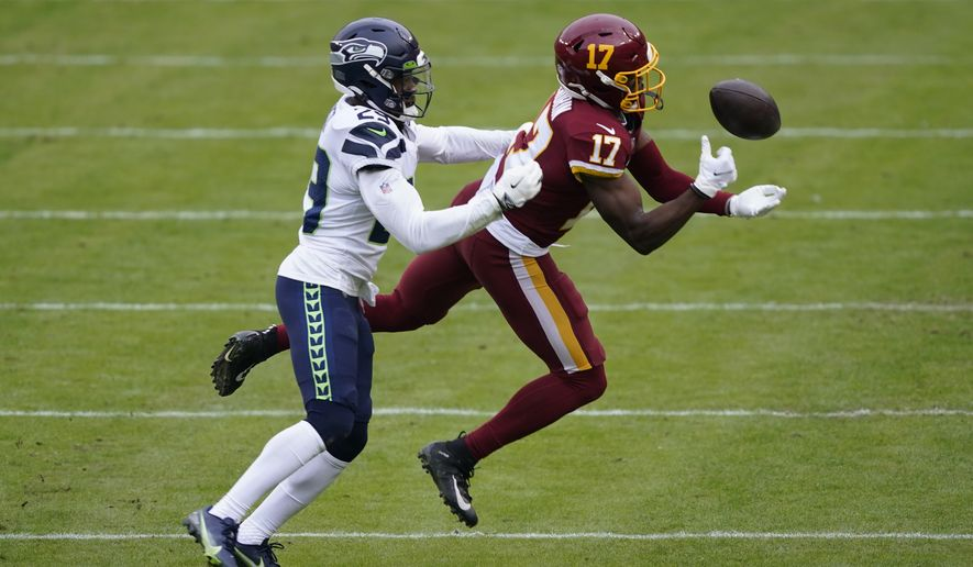 Washington Football Team wide receiver Terry McLaurin (17) juggles with a ball and unable to make the catch while being covered by Seattle Seahawks free safety D.J. Reed (29) during the first half of an NFL football game, Sunday, Dec. 20, 2020, in Landover, Md. (AP Photo/Susan Walsh)