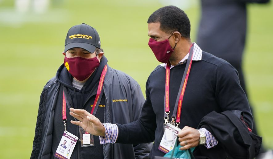 Washington Football Team owner Dan Snyder, left, walking on the field with Team President Jason Wright, right, before the start of an NFL football game against the Seattle Seahawks, Sunday, Dec. 20, 2020, in Landover, Md. (AP Photo/Susan Walsh) **FILE**