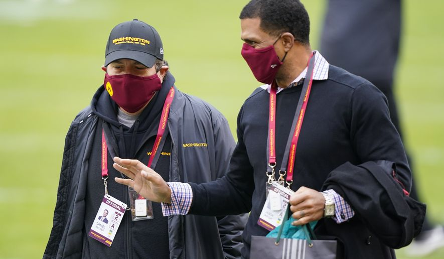 Washington Football Team owner Dan Snyder, left, walking on the field with Team President Jason Wright, right, before the start of an NFL football game against the Seattle Seahawks, Sunday, Dec. 20, 2020, in Landover, Md. (AP Photo/Susan Walsh)