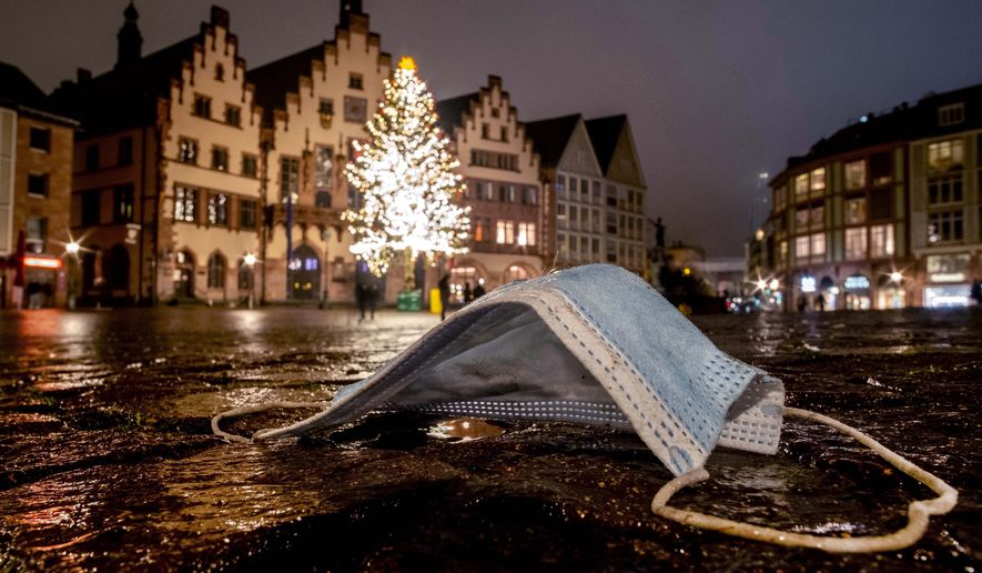 A discarded face mask is seen on the Roemerberg square with the Christmas tree in Frankfurt, Germany, Sunday, Dec. 20, 2020. (AP Photo/Michael Probst)