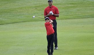 Tiger Woods watches his son Charlie's shot from the third fairway during the final round of the PNC Championship golf tournament, Sunday, Dec. 20, 2020, in Orlando, Fla. (AP Photo/Phelan M. Ebenhack)