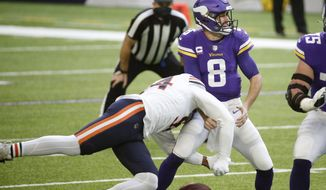 Minnesota Vikings quarterback Kirk Cousins (8) fumbles as he is hit by Chicago Bears linebacker Robert Quinn, left, during the first half of an NFL football game, Sunday, Dec. 20, 2020, in Minneapolis. (AP Photo/Bruce Kluckhohn)