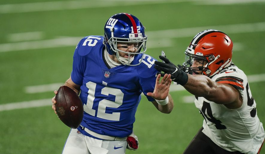 New York Giants quarterback Colt McCoy (12) evades Cleveland Browns' Olivier Vernon (54) during the first half of an NFL football game, Sunday, Dec. 20, 2020, in East Rutherford, N.J. (AP Photo/Seth Wenig) **FILE**
