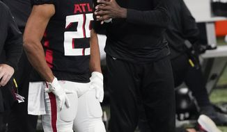 Atlanta Falcons Julio Jones, right, speaks with Atlanta Falcons running back Ito Smith (25) during the second half of an NFL football game against the Tampa Bay Buccaneers, Sunday, Dec. 20, 2020, in Atlanta. (AP Photo/John Bazemore)