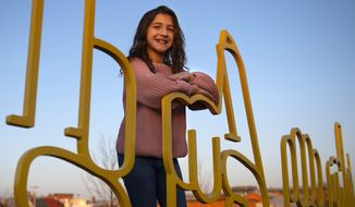 "Savannah Dahan, 10, poses at the bike rack crafted to spell ""Frederick"" in American Sign Language along Carroll Creek at S. East street on Dec. 10, 2020, in Frederick, Md. Dahan recently gained notoriety through signing ASL to songs and appearing in a deaf-friendly Hallmark commercial. (Graham Cullen/The Frederick News-Post via AP)"