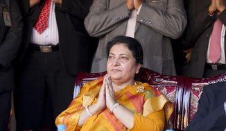 Nepali President Bidya Devi Bhandari pays respect during the opening ceremony of a traveling exhibition on Lumbini, Nepal in Yangon, Myanmar on Oct. 19, 2019. Nepal's president has dissolved Parliament after the prime minister made the recommendation amid an escalating feud within his Communist Party that is likely to push the Himalayan nation into a political crisis. Parliamentary elections will be held on April 30 and May 10, according to a statement from Bhandari's office. (AP Photo/Thein Zaw)