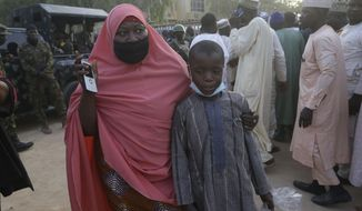 A mother is reunited with her freed schoolboy son who was among the kidnapped students in Katsina, Nigeria Friday, Dec. 18, 2020. More than 300 schoolboys kidnapped last week in an attack on their school in northwest Nigeria have arrived in the capital of Katsina state to celebrate their release. The boys were abducted one week ago from the all-boys Government Science Secondary School in Kankara in Katsina state village. (AP Photo/Sunday Alamba)