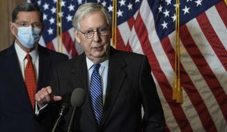 In this Tuesday, Dec. 15, 2020, photo, Senate Majority Leader Mitch McConnell, of Kentucky, speaks during a news conference with other Senate Republicans on Capitol Hill in Washington, while Sen. John Barrasso, R-Wyoming, listens at left. (Nicholas Kamm/Pool Photo via AP) ** FILE **