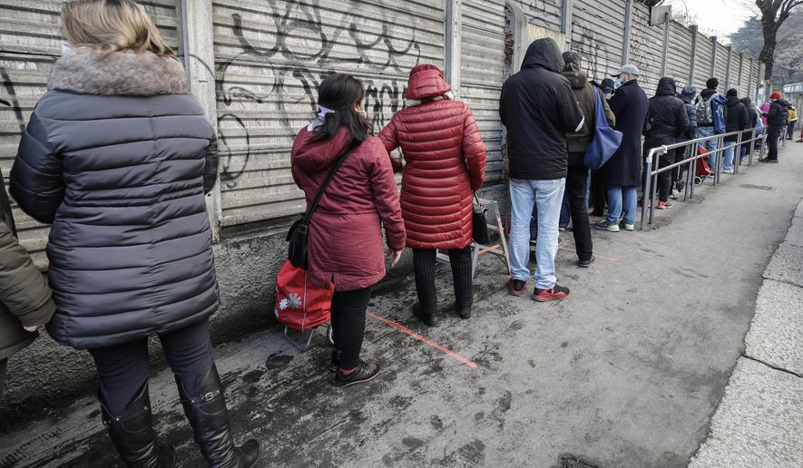 """People queue for food at the 'Pane Quotidiano' (Daily Bread) Onlus, in Milan, northern Italy, Thursday, Dec. 17, 2020. Nowhere in Italy is poverty more evident than in Lombardy, the northern region that has been the pandemic epicenter in both surges. The Coldiretti agriculture lobby estimates that the virus has created 300,000 so-called """"new poor,'' based on surveys of the dozens of charity associations operating in the region. (AP Photo/Luca Bruno)"""