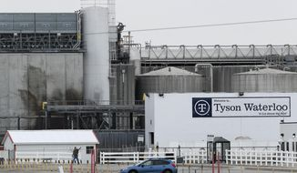 In this Friday, May 1, 2020, photo, a worker leaves the Tyson Foods plant in Waterloo, Iowa. The coronavirus devastated the nation's meatpacking communities in Iowa, Nebraska, and Minnesota earlier in the year.  (AP Photo/Charlie Neibergall, File)  **FILE**