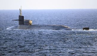 In this photo made available by the U.S. Navy, the guided-missile submarine USS Georgia transits the Strait of Hormuz in Persian Gulf, Monday, Dec. 21, 2020. The USS Georgia traversed the strategically vital waterway between Iran and the Arabian Peninsula on Monday, the U.S. Navy said, a rare announcement that comes amid rising tensions with Iran. (Mass Communication Specialist 2nd Class Indra Beaufort/U.S. Navy via AP)