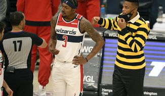 Washington Wizards guard Russell Westbrook, wears a facemask to protect against Covid-19, and guard Bradley Beal (3) talk with an official during the first half of a preseason NBA basketball game against the Detroit Pistons, Thursday, Dec. 17, 2020, in Washington. (AP Photo/Nick Wass)
