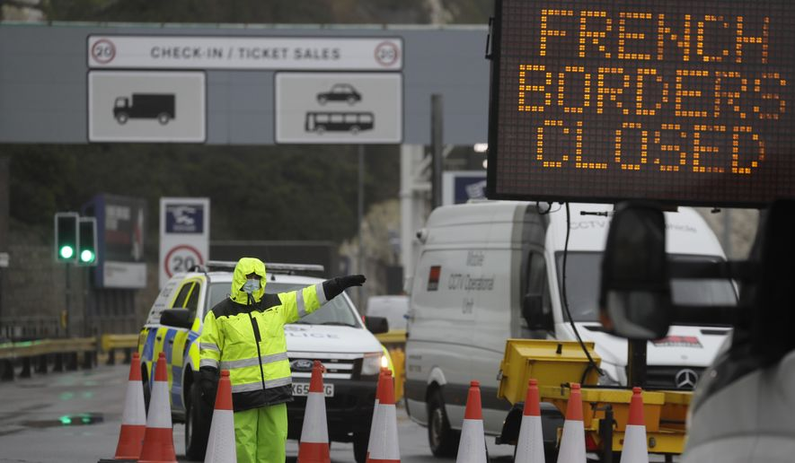 Security guard the entrance to the ferry terminal in Dover, England, Monday, Dec. 21, 2020, after the Port of Dover was closed and access to the Eurotunnel terminal suspended following the French government's announcement. France banned all travel from the UK for 48 hours from midnight Sunday, including trucks carrying freight through the tunnel under the English Channel or from the port of Dover on England's south coast. (AP Photo/Kirsty Wigglesworth)