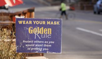 A sign advises visitors along Washington Street to wear face masks to try and reduce the spread of the coronavirus late Monday, Dec. 21, 2020, in downtown Golden, Colo. (AP Photo/David Zalubowski)