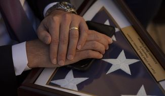"A staff member with U.S. White House Senior Adviser Jared Kushner holds a souvenir flag after U.S. Ambassador to Israel David Friedman, unveiled a plaque at the U.S. embassy in Jerusalem, designating the ""Kushner Courtyard,"" in honor of Kushner, Monday, Dec. 21, 2020. (AP Photo/Maya Alleruzzo, Pool)"