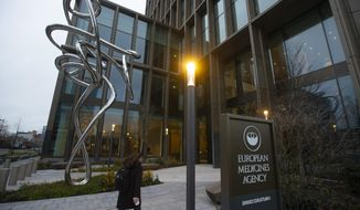 A person enters the European Medicines Agency in Amsterdam, Netherlands, Monday, Dec. 21, 2020, where the EMA's human medicines committee is holding an exceptional, fully virtual, meeting to conclude the evaluation of the Pfizer-BioNTech COVID-19 vaccine. (AP Photo/Peter Dejong)