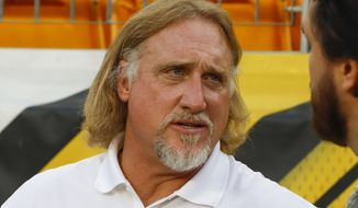 FILE - In this Sept. 30, 2019, file photo, Pro Football Hall of Fame outside linebacker Kevin Greene stands on the sideline during warmups before an NFL football game between the Pittsburgh Steelers and the Cincinnati Bengals in Pittsburgh. Hall of Fame linebacker Greene, considered one of the fiercest pass rushers in NFL history, has died. He was 58. Greene died Monday, Dec. 21, 2020, the family confirmed, as did the Pro Football Hall of Fame. (AP Photo/Gene J. Puskar, File)