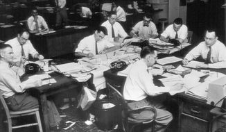 This undated file photo shows men in the newsroom of the The Kansas City Star on 18th Street and Grand Avenue in Kansas City, Mo. On Sunday, Dec. 20, 2020, the newspaper's top editor apologized for past decades of racially biased coverage and has posted a series of stories examining how it ignored the concerns and achievements of Black residents and helped keep Kansas City segregated. (The Kansas City Star via AP)