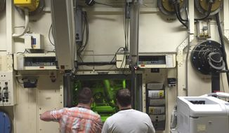 FILE - In this May 11, 2015, file photo, Colt Killian, left, and Rob Cox manipulate radioactive material remotely behind a protective barrier at the Hot Fuel Examination Facility at the Idaho National Laboratory near Idaho Falls, Idaho. Idaho is the top choice for the first new nuclear test reactor in the U.S. in decades. The U.S. Department of Energy on Monday, Dec. 21, 2020, released a draft environmental impact statement saying the Idaho National Laboratory is its preferred site for the proposed Versatile Test Reactor. (AP Photo/Keith Ridler, File)