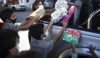 "Children receive Christmas presents donated by the volunteer group ""Un Juguete, Una Buena Noticia,"" or One Toy, One Good News, from the back of a pick-up truck in Caracas, Venezuela, Friday, Dec. 18, 2020. The volunteer group is made up of journalists and other media workers who collect donations and hand out toys to poor children. (AP Photo/Ariana Cubillos)"