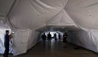 Engineers and volunteers help build a mobile field hospital at UCI Medical Center, Monday, Dec. 21, 2020, in Orange, Calif. California's overwhelmed hospitals are setting up makeshift extra beds for coronavirus patients, and a handful of facilities in hard-hit Los Angeles County are drawing up emergency plans in case they have to limit how many people receive life-saving care. (AP Photo/Jae C. Hong)