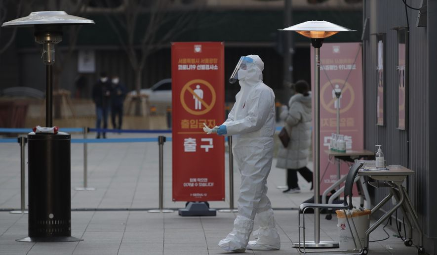 A medical worker wearing protective gears prepares to take sample in the sub-zero temperatures at coronavirus testing site in Seoul, South Korea, Monday, Dec. 21, 2020. (AP Photo/Lee Jin-man)