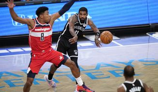 Brooklyn Nets guard Kyrie Irving (11) passes to Brooklyn Nets forward Kevin Durant (7) as Washington Wizards forward Rui Hachimura (8) defends Irving during the second quarter of a preseason NBA basketball game, Sunday, Dec. 13, 2020, in New York. (AP Photo/Kathy Willens)