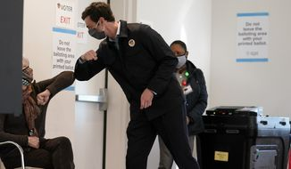 Democratic nominee for U.S. Senate from Georgia Jon Ossoff greets a poll worker after voting early in Atlanta on Tuesday, Dec. 22, 2020. For the second time in three years, Jon Ossoff is campaigning in overtime. The question is whether the 33-year-old Democrat can deliver a win in a crucial Jan. 5 runoff with Republican Sen. David Perdue. (AP Photo/John Bazemore)