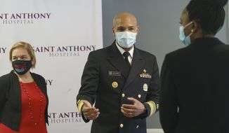 U.S. Surgeon General Jerome Adams, center, is joined by Chicago Health Commissioner Dr. Allison Arwady, left, and Illinois Public Health Director Dr. Ngozi Ezike during their visit at Saint Anthony Hospital in Chicago, Tuesday, Dec. 22, 2020. (Youngrae Kim/Chicago Tribune via AP, Pool)