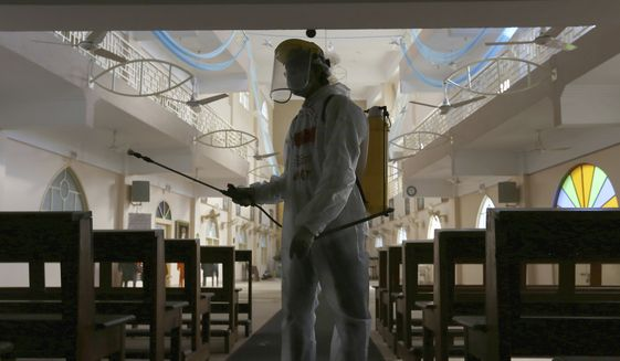 A volunteer sprays disinfectant in the main hall of St Paul's Parish in an effort to curb the spread of the coronavirus, ahead of Christmas celebrations, in Karachi, Pakistan, Tuesday, Dec. 22, 2020. (AP Photo/Fareed Khan) ** FILE **