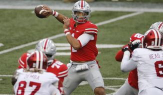 FILE - In this Nov. 21, 2020, file photo, Ohio State quarterback Justin Fields throws a pass against Indiana during the first half of an NCAA college football game in Columbus, Ohio. Fields repeated as offensive player of the year and is joined by three of his teammates on the Associated Press All-Big Ten football team. (AP Photo/Jay LaPrete, File)